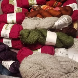 View of a container of stashed yarn, including red, green, purple, and grey skeins of different sizes.