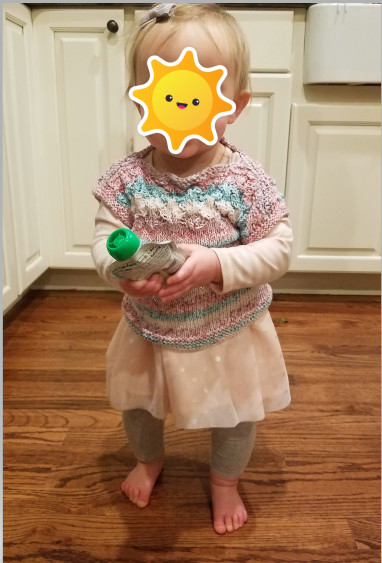 Sunshine is standing holding an apple sauce pouch.  She is wearing a pink party dress with grey leggings and a hand-knit tee in pink and teal stripes over it.