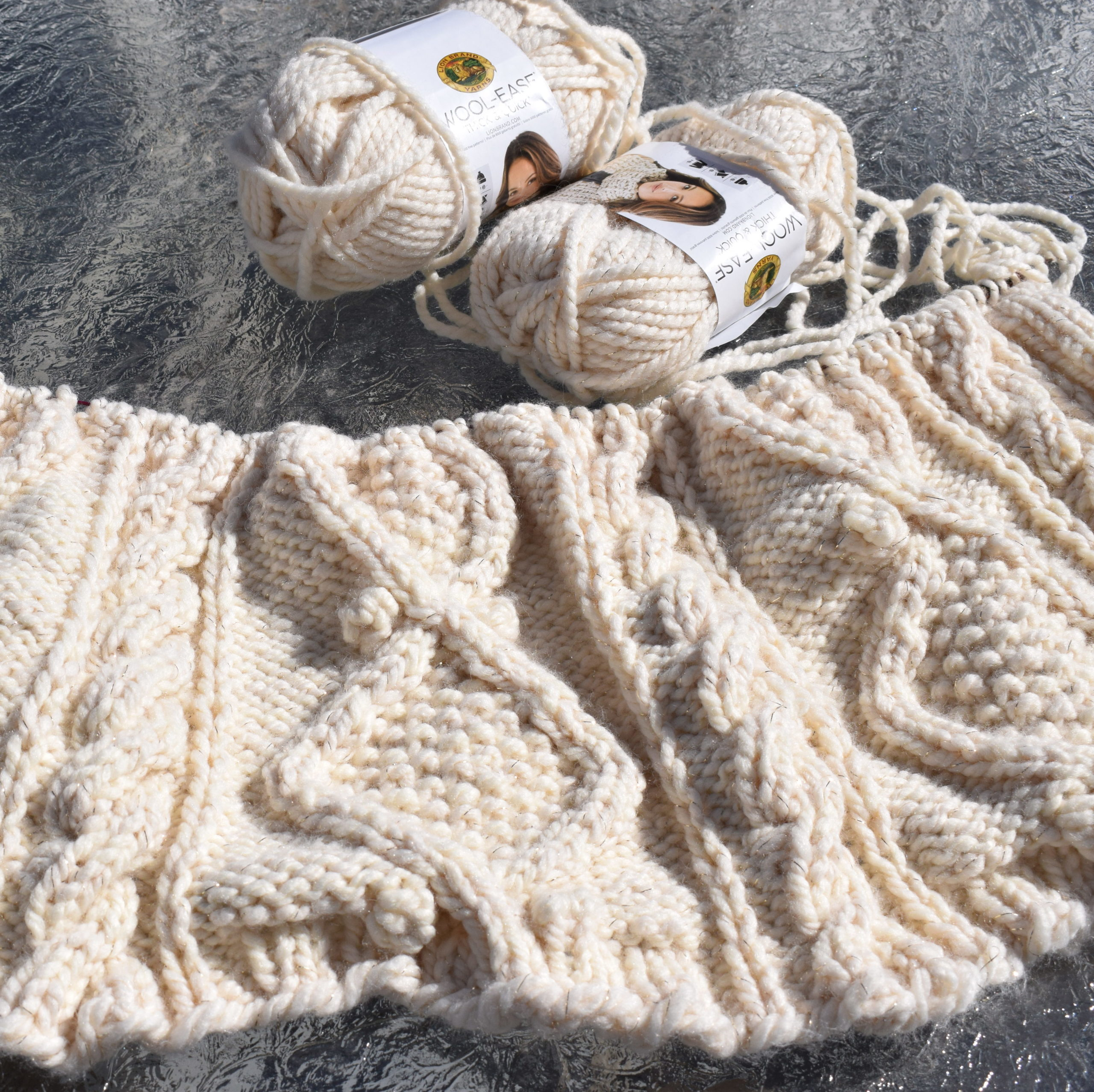 A partially-completed, deeply textured afghan knit in a bulky cream yarn.  Squishy cables bracket stitches forming large diamonds with seed stitch centers.  Two skeins of yarn are lying next to the work.