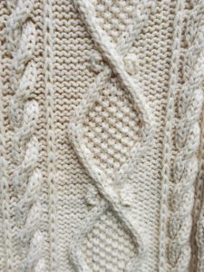 A close-up of the completed afghan, showing the seed stitch diamonds and bordering cable twists, worked in a cream colored yarn.