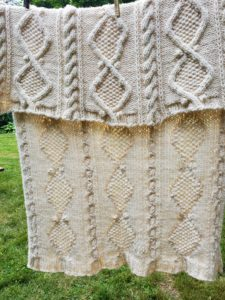 View of the finished afghan hanging on a clothesline to dry, showing both the front and reverse of the cables.
