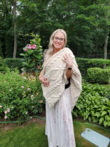 Alecia, the writer's cousin, poses in a garden wearing a white lace dress and black glasses.  She has draped her new white cabled afghan over one shoulder and is hugging it to herself.