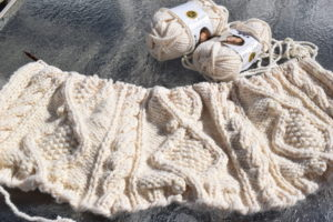 Blanket in progress is stretched across a table in the sunlight with two skeins of yarn laying next to it.
